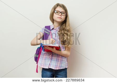 Young Schoolgirl In Glasses And With A Backpack Writes In A School Notebook. Background Bright Wall