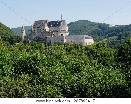 The Magnificent Chateau Dé Vianden In Luxembourg In The Hills Covered In Forest Trees On A Sunny Sum