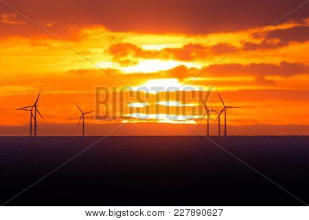 Sunset At Wind Turbines Windmills Offshore Clean Power Farm Near. Many Energy Stations On Sea Water,