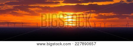 Panorama Sunset Sun At Windmills Offshore Clean Wind Power Farm. Many Energy Stations On Sea Water,