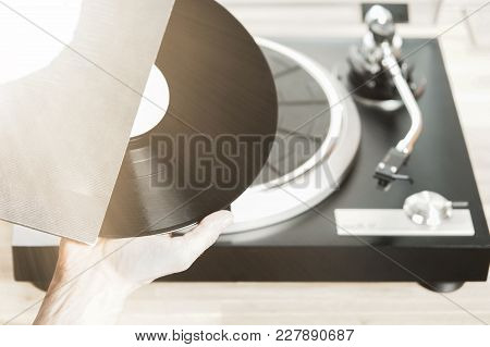 Hand Pulls Vinyl Record Out Of Its Cover For Listening To Records.
