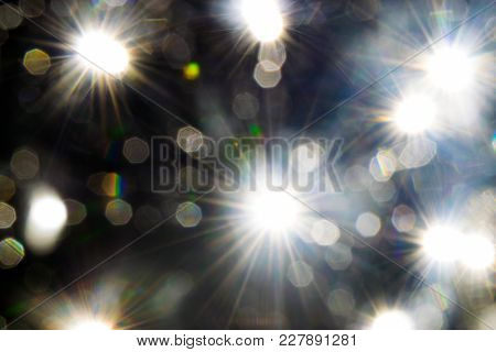 Light Beams Reflecting Through The Glass Bubbles Formatting The Star Beam Shape In Black Background.