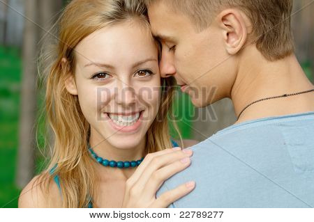 Smiling teenage girl with her boyfriend at the park