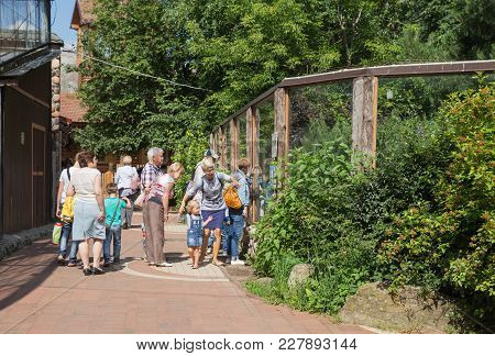Saint Petersburg, Russia - July 26, 2017: People In A Zoo Near An Enclosure With Wolves Look At Anim