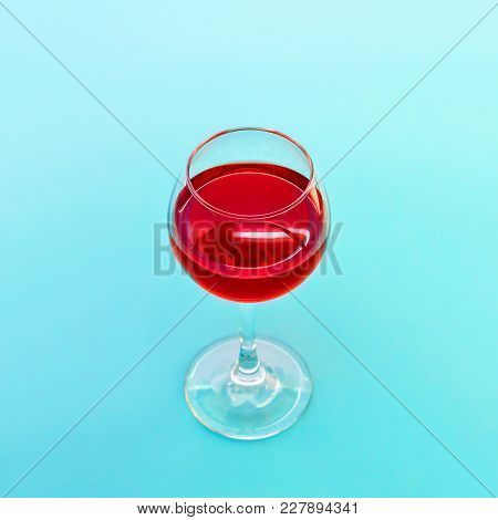A Glass Of Red Wine On Blue Background