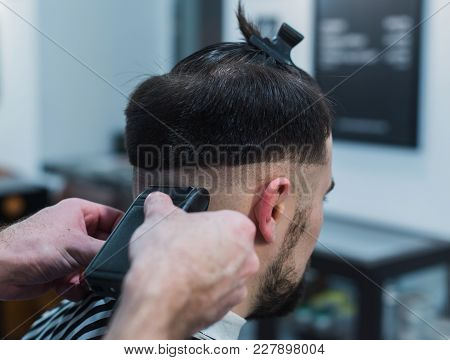 Male Barber Giving Client Haircut In Barber Shop