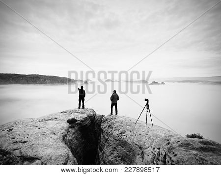 Two Warm Coat Photographers With Tripod Shoot Pictures Of Autumnal Landscape Below Mountain.  Rainy