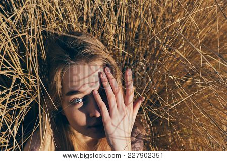Young Blue-eyed Girl Blonde Covers Her Face From The Sun, Lies In The Field