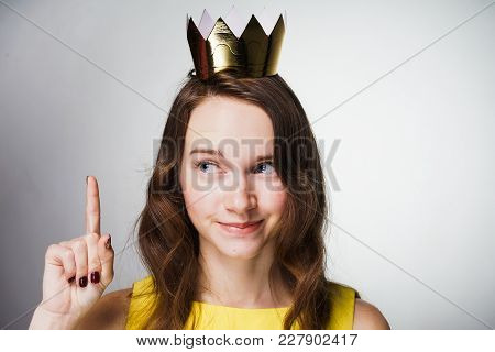 A Cute Young Girl In A Yellow Dress Lifted Her Index Finger Up, A Golden Crown On Her Head, An Idea