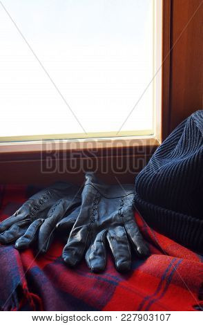 Dark Blue And Red Checked Woolen Scarf, Black Leather Gloves And Black Knitted Hat On Windowsill. Wi