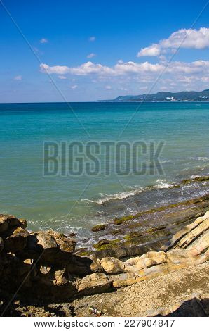 Rocky Sea Shore With Pebble Beach, Transparent Waves With Foam, On A Warm Summer Day