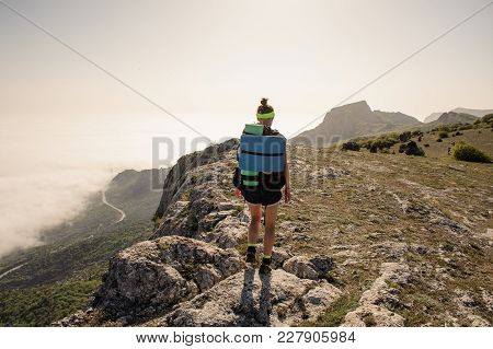 Beautiful Slender Girl In A Bright Sports Uniform Stands On The Edge Of A Forested Cliff Against The