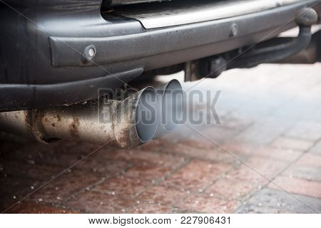 Double Exhaust From An Older Car With Diesel Engine Blows Out Gas With High Particulate Matter Pollu