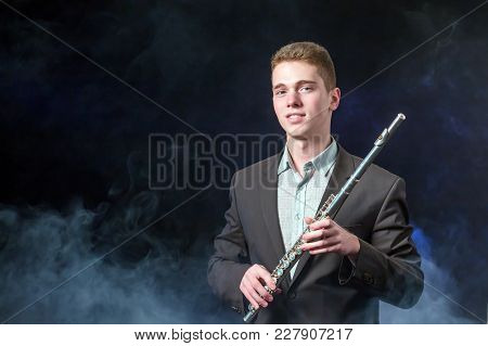 A Handsome Guy In A Gray Jacket Holds A Flute In His Hands. Smoke On A Dark Background. Copy Space.