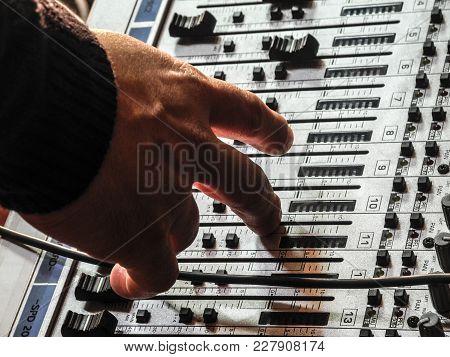 Hand Adjusting Sound Mixer Settings Close Up
