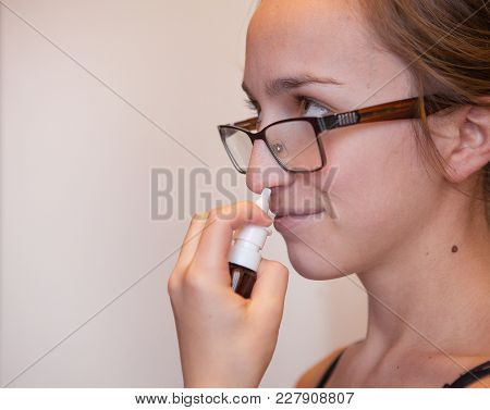A Woman With A Runny Nose Holds A Medicine In Her Hand, A Red Nose.