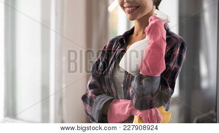 Happy female cleaner looking satisfied at shiny washed glass after work, purity, stock footage poster