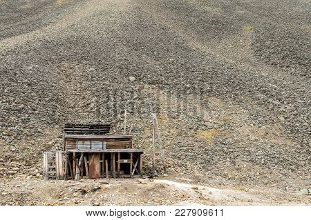 Old Building Used For The Coal Mining Industry At Svalbard. Landscape Of Glacial Moraine Rocks In Th