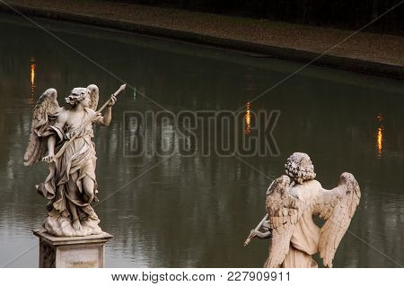 Two Statues Of Angels Of Bridge Of Angels Against The Background Of The River In Rome. Italy