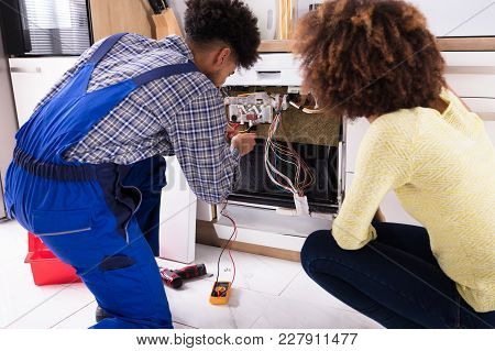Woman Looking At Male Technician Checking Dishwasher With Digital Multimeter In Kitchen