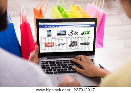 Close-up Of A Couple Shopping Online In Front Of Multi Colored Shopping Bags At Home