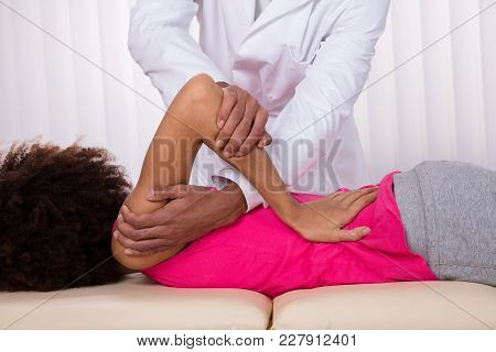 Physiotherapist Stretching Female Patient Shoulder