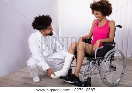 Male Physiotherapist Examining Leg Of Female Patient Sitting On Wheelchair