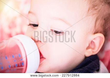 Cute Baby Boy Is Drinking Water From Plastic Bottle Sitting On Chair. Close Up Portrait.