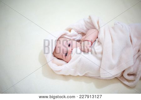 Cute Baby Wrapped Towel After Bathing. Closeup Portrait.