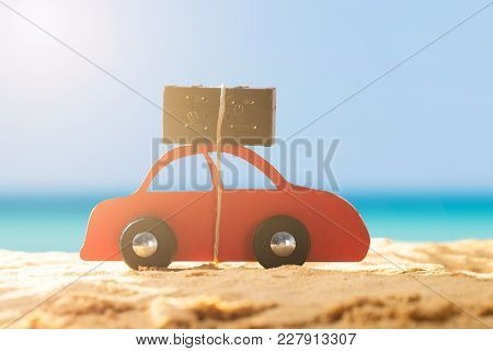 Close-up Of A Red Car With Luggage On Sandy Beach During Sunny Day