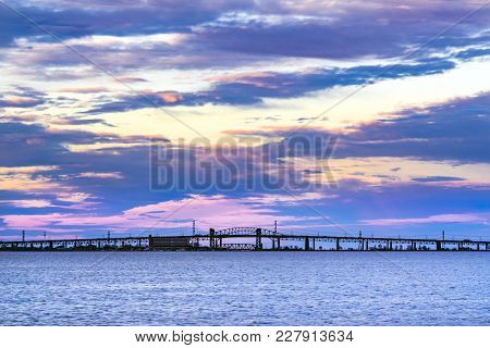 Beautiful Violet, Blue And Yellow Sunset Over Long Silhouetted Skyway Bridge, Bay Of Water In Foregr