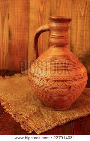 Old Ceramic Jug. Pitcher Ceramic On Sacking. Decanter Ceramic Brown On Sacking. Old Crockery On Deco