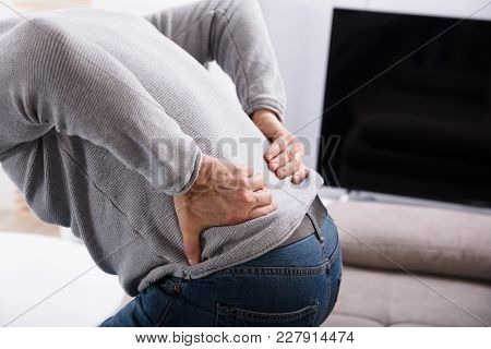 Mid Section View Of A Man Suffering From Back Pain