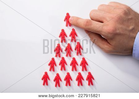 Red Human Figures Arranged In Triangular Shape