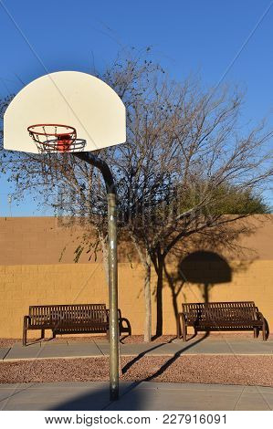 An Outdoor Basketball Hoop, Backboard, And Standard Are Reflected Against A Brick Wall.