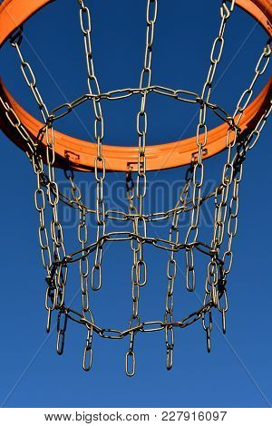 An Outdoor Basketball Rim And Chain Net With A Blue Sky Background