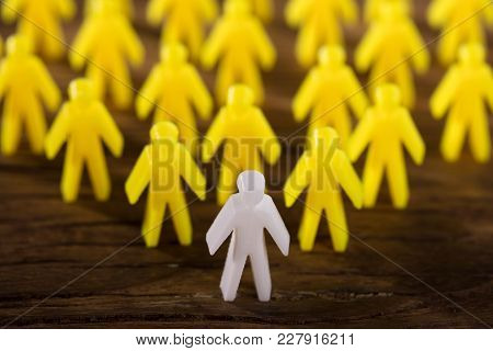 Elevated View Of White Figure Leading Yellow Human Figures On Wooden Background