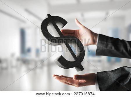 Closeup Of Business Woman In Black Suit Keeping Stone Dollar Sign In Hands With Office View On Backg