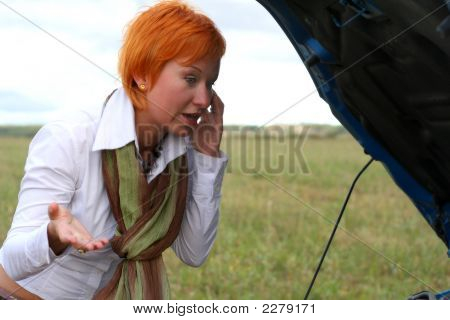 Young Red-Haired Woman With Her Broken Car With Mobile Phone. The Girl Have A Big Problem