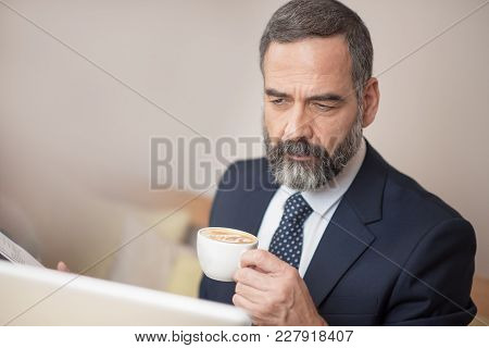 Senior Mature Business Man Having A Coffee In A Coffee Shop And Working On His Computer