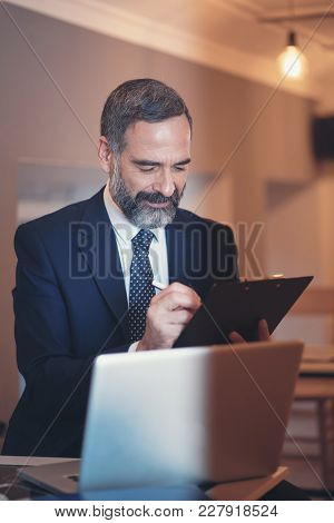 Senior Elderly Business Man Filling Out Some Paper Work, Drinking Coffee In A Cafe