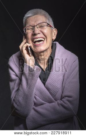 Senior Lady Laughing On Her Cell Phone, Having A Cheerful Conversation With A Friend
