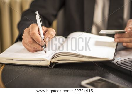 Senior Elderly Business Man Writing Down Credit Card Information, Making Some Calculations