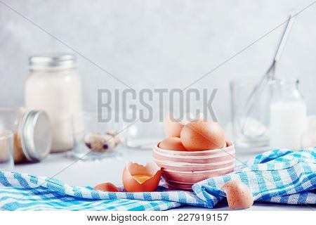 Brown Eggs In A Ceramic Bowl On A Light Background With Milk, Flour And Ingredients For Easter Cooki
