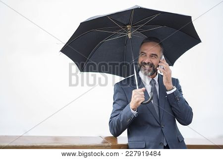 Business Man On A Rainy Day, Chatting With A Colleague And Holding An Umbrella