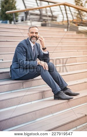 Senior Businessman Relaxing In An Urban Area, Having A Break From Work