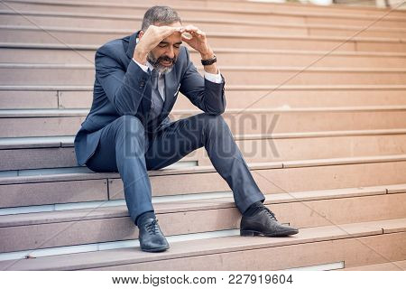 Stressed And Overwhelmed Senior Businessman Is Trying To Release The Tension, Sitting On The Stairs