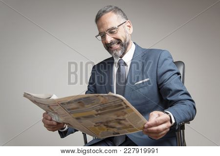 Happy Senior Business Man Reading Newspaper, Amused With Its Content