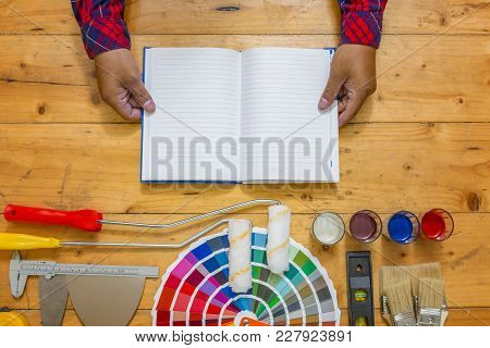 Hands Holding Diy Training Open Manual With Work Tools, Color Swatches And Painting Rollers At Botto