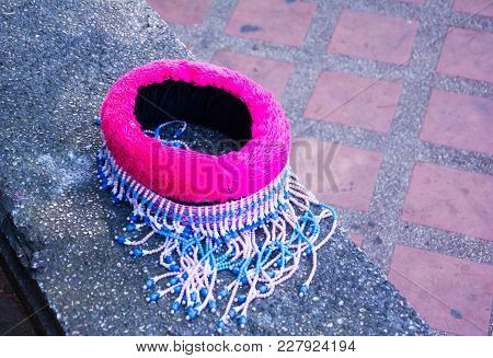 Knitted Hat From Colorful Fabric , Blue And Pink. It Placed On A Stone Bench. This Is A Hat For Chil